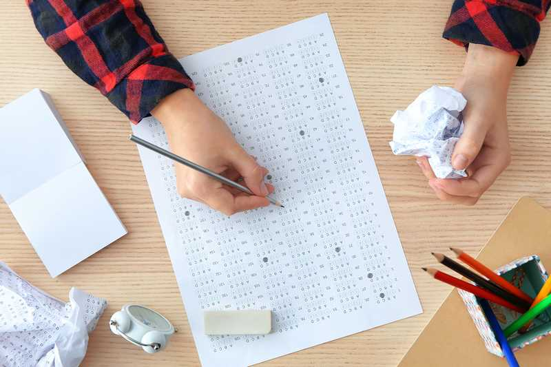 Student choosing answers in test form to pass exam at table